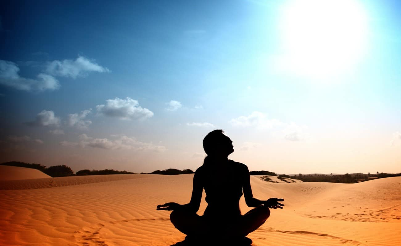 Woman in desert, meditating - Yoga classes New York
